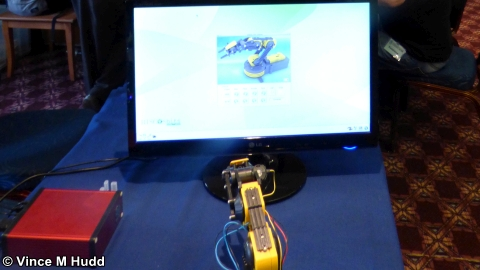 The robot arm on the MUG stand admiring itself on screen at Wakefield 2018